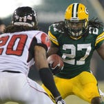 Green Bay Packers running back Eddie Lacy (27) stares down Atlanta Falcons safety Dwight Lowery (20) on a long run during the first quarter of Monday night's game at Lambeau Field.