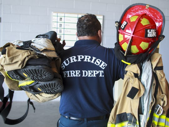 A Surprise fire captain carries his turnouts as he