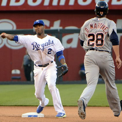 Kansas City Royals shortstop Alcides Escobar (2) turns a double play in the sixth inning against Detroit Tigers left fielder J.D. Martinez.