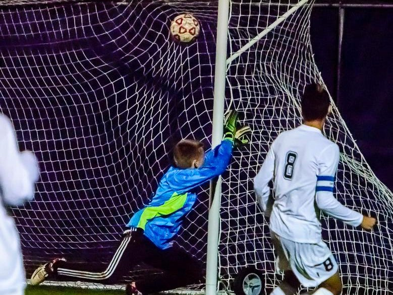 Quinton Hay ,8, of East Lansing watches his kick sail into the net past St. Johns goalie Brett Post to put East Lansing up 3-0 in the 2nd half of their Division 2 district semifinal game Thursday October 22, 2015 in East Lansing.
