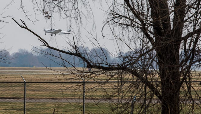 A plane is framed through the trees along the fence line at Bowman Field near Pee Wee Reese Road on Wednesday. Dec. 14, 2016