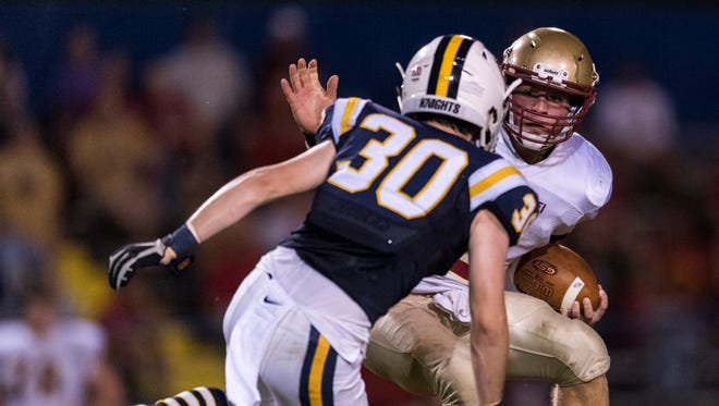 Mater Dei's Chase Rheinlander (9) avoids a tackle by Castle's Kyle Tenison (30) at John Lidy Field in Newburgh, Ind., on Friday, Sept. 22, 2017. The Wildcats defeated the Knights, 31-30.