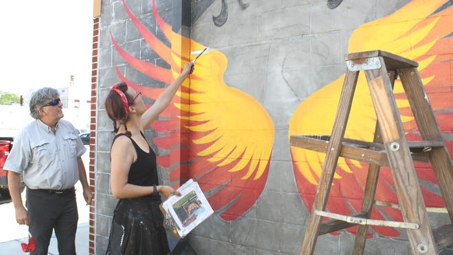 Gene Harrison and muralist Heidi Wolfe work out the details of her latest artwork -- an interactive mural on the back wall. It is accessible from the parking lot between North Street and north Nottawa Street.