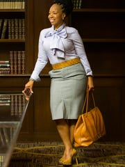 Toni Howard wears a Banana Republic blue-and-white stripe bow tie shirt; Banana Republic grey pencil skirt; and Limited camel colored belt.