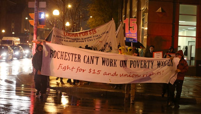 Protestors turned out, despite the rain, to march from Washington Square Park to City Hall as part of a nationwide demand for a $15 an hour wage for fast food workers, Tuesday in Rochester, Nov. 10, 2015.
