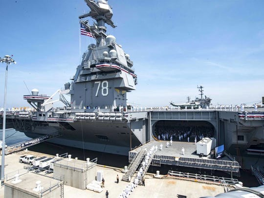 Sailors man the rails of the aircraft carrier USS Gerald