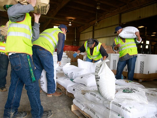 NAPI employees get ready to load a vehicle with potatoes and pinto beans during the company's customer appreciation day on Saturday at its Region 2 scales south of Farmington.