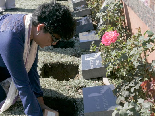 Tedi Patterson gently lowers the remains of baby Marguerite into a small grave during Saturday's memorial service for Marguerite and six other abandoned babies. The service was held Ivy Lawn Memorial Park in Ventura.