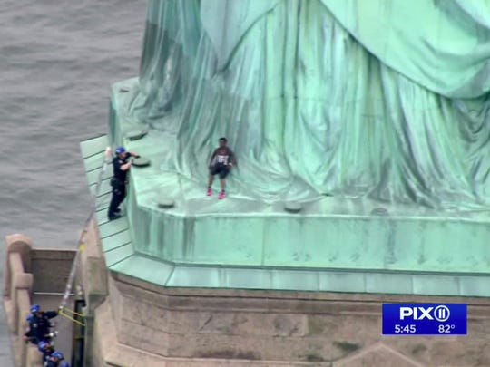In this image made from video by PIX11, a person, center, leans against the robes of the Statue of Liberty on Liberty Island, as one of the police officers climbed up on a ladder to stand on a ledge nearby talking the climber into descending in New York, Wednesday, July 4, 2018.