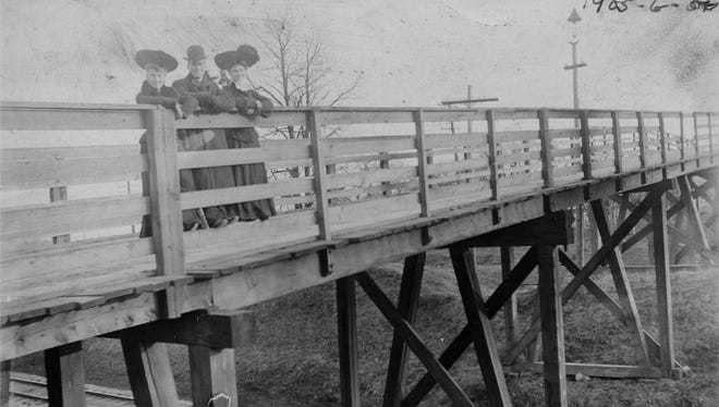 "Camel-Back Bridge, 1905: Estella Coleman, Lee Price, and Grace Engler are all dressed up to pose on the Camel-Back Bridge over the railroad tracks on Morrison Road. This early photo shows how the narrow bridge got its name.  It was replaced by a wider wooden bridge that burned in the 1980s, and then the current modern Camel-Back was constructed, minus most of its ""hump."""
