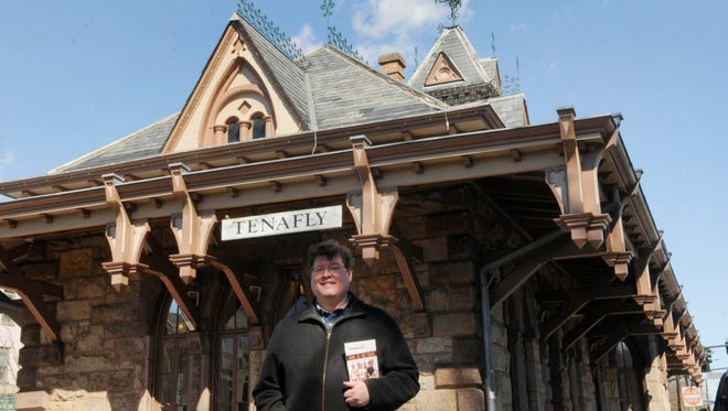 Paul Stefanowicz with a copy of his book at the former Tenafly train station.