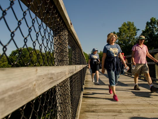 Walkers cross the old trestle bridge Monday, Sept. 5, during the annual Trestle Trek along the Wadhams to Avoca Trail.