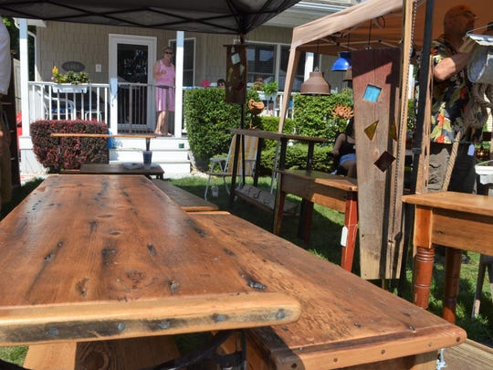 Tables made from reclaimed wood sit in Joe Male's stall at the Lexington Art Fair on Aug. 5, 2018, in Lexington, Michigan.