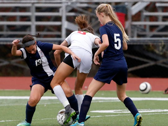 Edison's Grace De Araujo (center) battles with Dunellen's Sasha Rodriguez (left) and Faith Wright during their GMC Tournament preliminary round game on Thursday.
