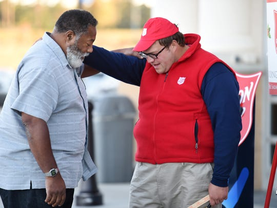 Salvation Army bell ringer Samuel Harrison, right, prays with Willie Earl Gray of Carthage outside the Sam's Club in Madison on Thursday. Harrison, who likes to sing as he's ringing his bell, frequently shares a kind word or a message of faith with those he encounters at his post by the familiar red kettle.