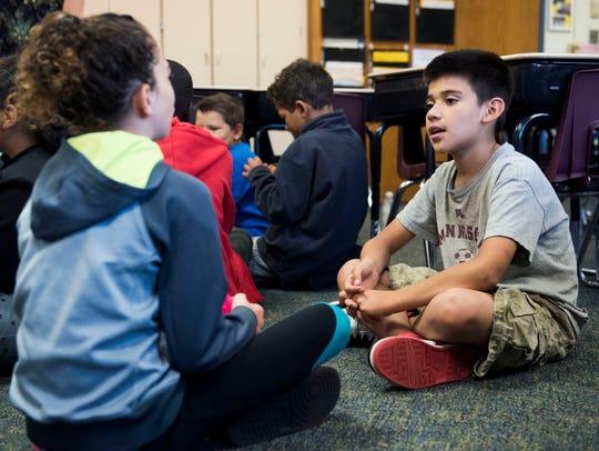 Fourth-grader Jan Nunez talks a classmate with at Laura