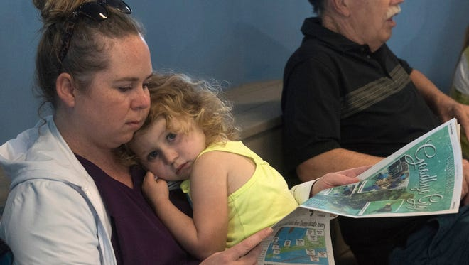 Brittany Naggatz Ramage and her daughter, Andi, look over a commemorative newspaper Tuesday, July 25, 2017, while attending a memorial service for Gigi, the former resident sea turtle at the Navarre Beach Sea Turtle Conservation Center. Gigi was named after Ramage's mother, Gigi Naggatz.