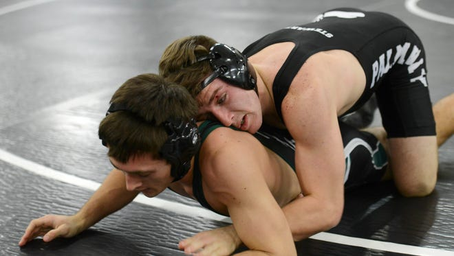 Shane Stewart of Palm Bay takes on Melbourne's Chandler Holder during the Cape Coast Conference wrestling tournament.