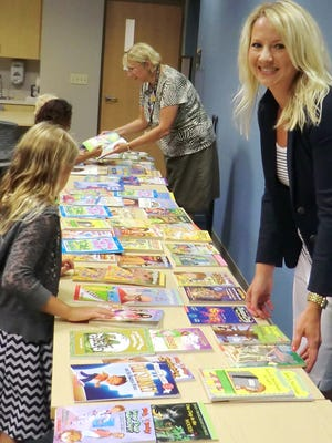 Charity Club President Trisha Krug, right, and Library Assistant Julia Cartwright help children at the YMCA day care to pick out new books as rewards for completing the library's summer reading program. The club's $1,000 donation to the library paid for the more than 800 books that have been handed out. Charity Club funded the summer reading program in 2013 as well, using proceeds from its annual Charity Ball. The ball — set for Friday, Dec. 5 — is the club's primary fund-raiser; the club donates all money raised to programs benefiting children in Fond du Lac County.