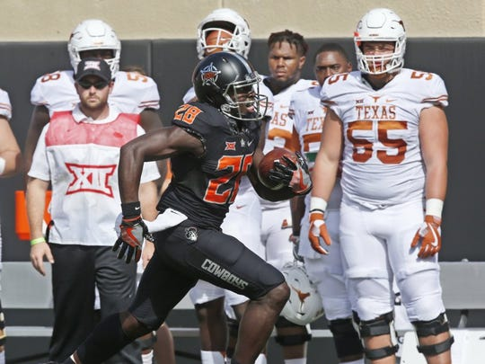 Oklahoma State wide receiver James Washington (28) runs past the Texas bench and into the end zone for a touchdown in the first quarter in Stillwater, Okla., Saturday, Oct. 1, 2016. (AP Photo/Sue Ogrocki)
