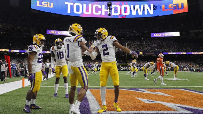 LSU wide receiver Ja'Marr Chase (1) celebrates with wide receiver Justin Jefferson on Jan. 13 after scoring during the first half of the NCAA College Football Playoff national championship game against Clemson in New Orleans. The SEC's university presidents on Thursday agreed on a 10-game schedule that eliminates all nonconference opponents and is set to begin Sept. 26. The SEC championship game, originally scheduled for Dec. 5, will be pushed back to Dec. 19.
