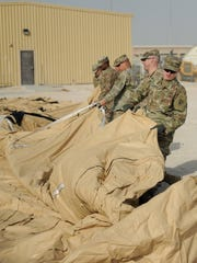 Soldiers from the deployed element with the 11th Air Defense Artillery Brigade headquarters unfold a tent as part of the brigade command post during an air missile defense exercise.