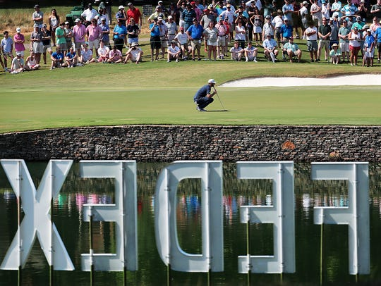 Dustin Johnson eyes a putt on the 14th hole during