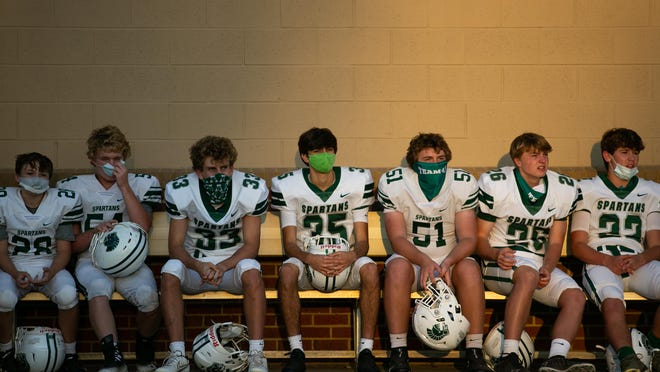 Members of Athens Academy sit prior to a GHSA high school football game between Athens Academy and Wesleyan in Norcross, Ga., on Friday, Oct. 16, 2020.