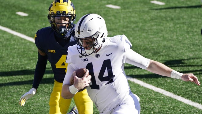 Penn State quarterback Sean Clifford, chased by Michigan defensive back Vincent Gray (4) runs for a 28-yard touchdown during the first half of an NCAA college football game, Saturday, Nov. 28, 2020, in Ann Arbor, Mich.