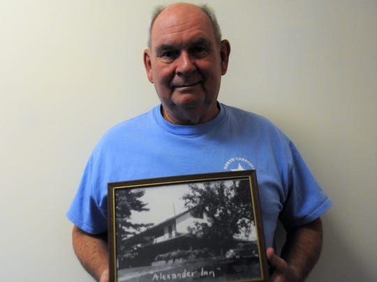 Bill Alexander holds a picture of the Alexander Inn in Swannanoa, where he recalls a spooky story about a regular guest.