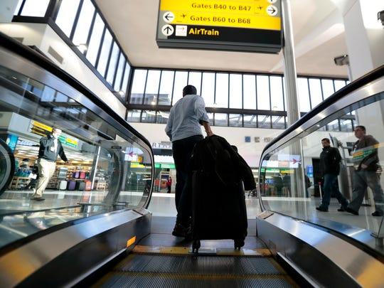 A traveler pulls luggage off an escalator at Newark