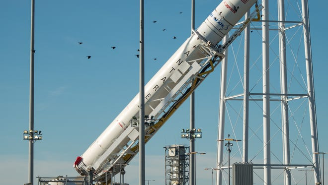 The Orbital ATK Antares rocket, with the Cygnus spacecraft onboard, is raised into the vertical position on launch Pad-0A, Friday, Oct. 14, 2016 at NASA's Wallops Flight Facility in Virginia.