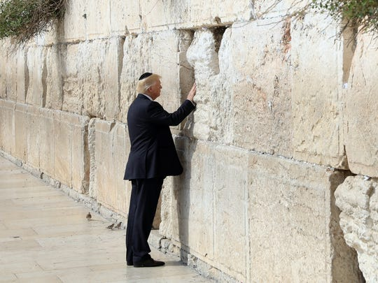 President Trump touches the Western Wall, Judaism's holiest prayer site, in East Jerusalem's Old City, May 22, 2017. He was the first sitting U.S. president to do so. Israel's claim to the area is disputed by Palestinians.