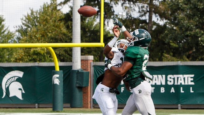 MSU CB Josh Butler and WR Cam Chambers fight for a ball during football practice Friday, August 4, 2017.  [MATTHEW DAE SMITH/Lansing State Journal]