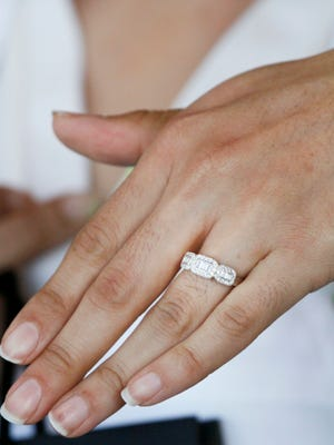 A bride-to-be tries on a wedding ring.