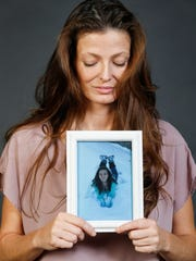 Serena Latham holds a picture of her daughter Camille