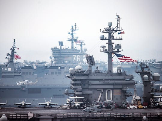 Aircraft sit on the flight deck of the aircraft carrier
