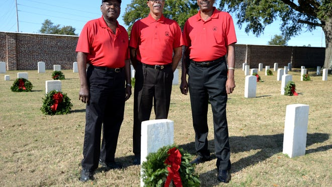 Par Four Charities members, from left, Walter Wallace, J.D. White and Raymond Griff stand next to one of 252 U.S. Colored Troops' gravestones Tuesday at Barrancas National Cemetery. Members of Par Four Charities joined Kiwanis Big Lagoon volunteers to place donated wreaths on Saturday as part of Wreaths Across America Day.