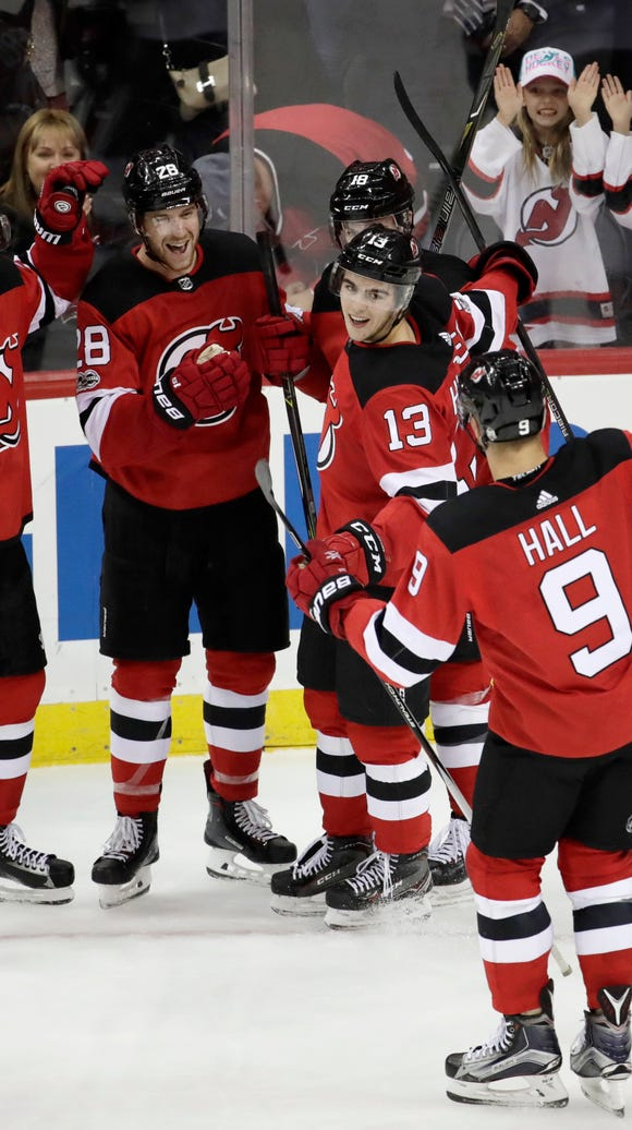 New Jersey Devils players celebrate a goal by Damon