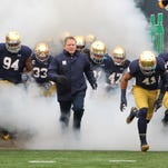 Nov 15, 2014; South Bend, IN, USA; Notre Dame Fighting Irish coach Brian Kelly leads the team onto the filed before the against the Northwestern Wildcats at Notre Dame Stadium. Mandatory Credit: Brian Spurlock-USA TODAY Sports