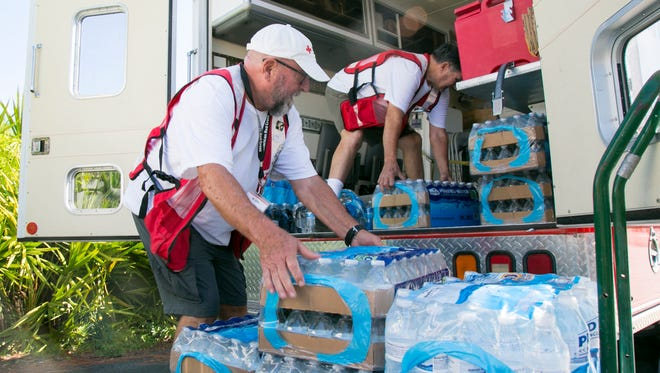 Donald Weaks, left, and Thomas Lee load water into the Red Cross Emergency Response Vehicle in south Fort Myers on Wednesday.