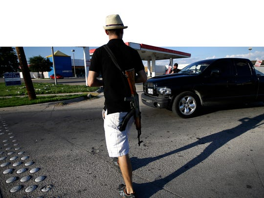 Kory Watkins, coordinator for Open Carry Tarrant County, carries his rifle during a May demonstration in Texas.