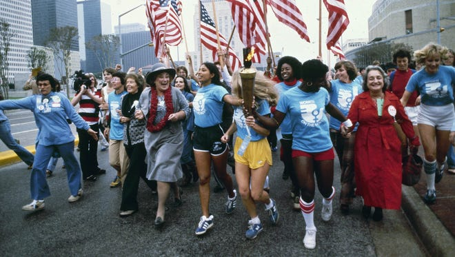 In this November 1977 file photo, leaders of the women's movement pass a torch that was carried by foot from New York to Houston, Texas, for the National Women's Convention. Among the marchers, from left foreground, are tennis star Billie Jean King, in blue shirt and tan pants;  U.S. Congresswoman Bella Abzug, wearing a hat; and feminist writer Betty Friedan, in a red coat.