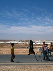 Syrian refugees walk near the Azraq Refugee Camp where