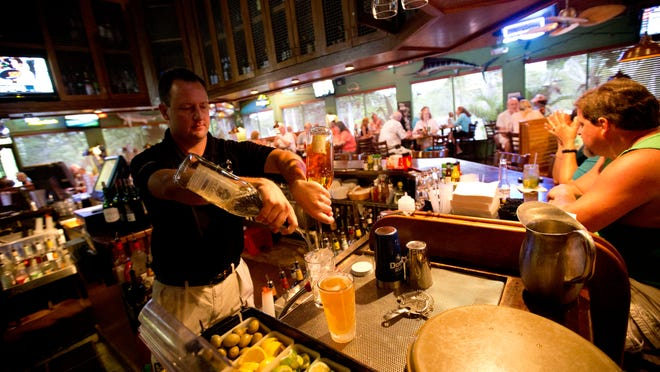 Justin Harris, a bartender for Doc Ford's Rum Bar and Grille pours a drink. As out-of-town guests descend, food critic Jean Le Boeuf has your guide for feeding them.