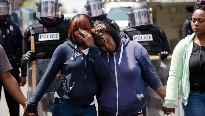 Jerrie Mckenny, center left, and her sister, Tia Sexton embrace as people sing the hymn Amazing Grace on Tuesday in Baltimore in the aftermath of rioting following Monday's funeral for Freddie Gray, who died in police custody.
