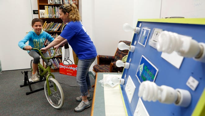 Fourth-grader Jessica DelDuca rides an energy bike as her teacher Jennifer Martini looks on at Sloatsburg Elementary School on Friday, May 15, 2015. Students learned the difference between incandescent and compact fluorescent/LED lights by pedaling during an environmental program called the Earth B.E.A.T. (Basic Environmental Awareness Training) facilitated by Keep Rockland Beautiful.