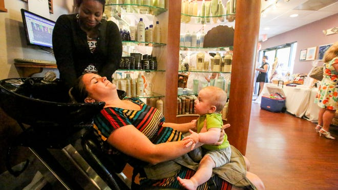 Becky Savage holds her son, Frankie, 5 months, as Kathleen Bathel, hair assistant, washes her hair. Love That Dress!7 kicked off its annual collection parties with the sixth annual SPADA-thon on Tuesday, May 19, 2015, at SPADA Salon & Day Spa. The event helped raise money and dresses for the PACE Center for Girls of Lee County and the Golisano ChildrenÕs Hospital of Southwest Florida.