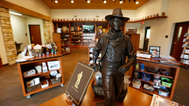 A John Wayne statue stands among the gift shop items Wednesday, May 6, 2015, inside the John Wayne Birthplace Museum in Winterset, Iowa.