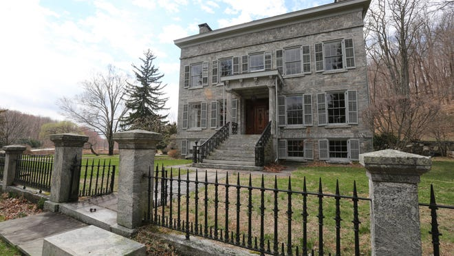 The 1849 house was constructed of meticulously cut local granite, and the same stone was used for the outbuildings and the stone and iron fence in front.
